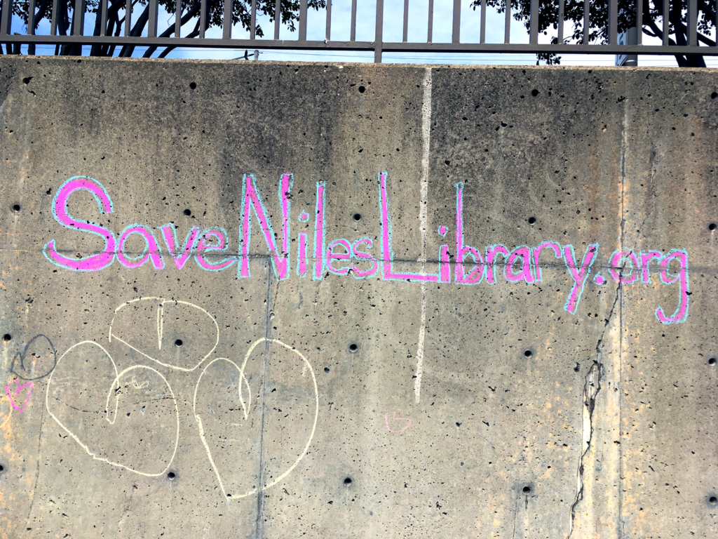 Chalk on a wall that reads # Save Niles Library.